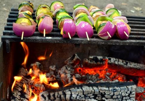 Veggie kabobs cooking over an open fire.