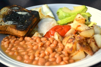 Baked beans, homefries, sliced avocado, over-easy eggs and slightly darkened gluten-free toast.