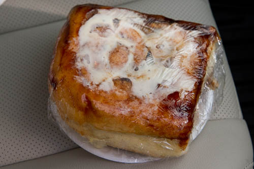Galactic Cinnamon Bun heated up in plastic wrap on a paper plate.